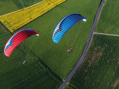 Gin Gliders Bolero 6 EN-A Gleitschirm im Flug über Felder mit Sitzgurtzeug.