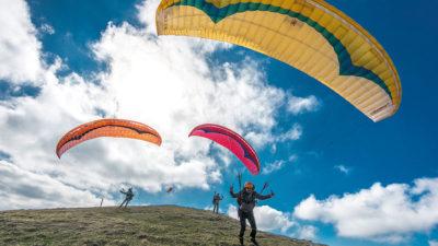 Anfänger Gleitschirm Gin Gliders Bolero 6 EN-A Gleitschirm. Das Bild zeigt drei Piloten beim Start.