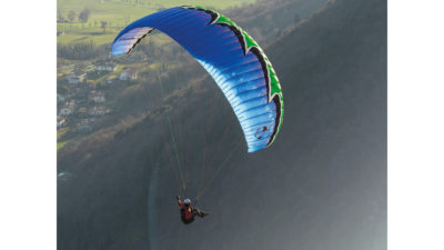 U-Turn Eternity EN-A Gleitschirm im Flug mit Sitzgurtzeug vor einem bewaldeten Berg
