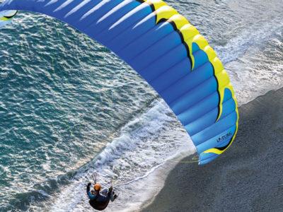 Leichtschirm U-Turn Everest Plus EN-C Gleitschirm im Flug über dem Strand mit Sitzgurtzeug