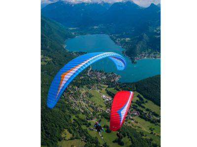 Das Bild zeigt den Gin Gliders Fuse 2. Bei dem Gleitschirm handelt es sich um einen Tandemschirm. Das Bild stellt den Schirm im Flug über einem See dar. Es handelt sich um einen Passagierflug oder auch Tandemflug. Auf dem Bild sind die Tandemschirme in zwei Farben.