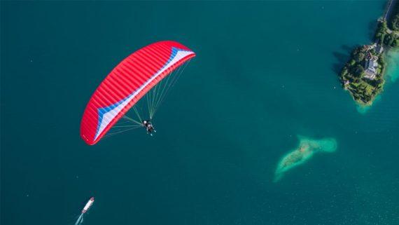 Das Bild zeigt den Gin Gliders Fuse 2. Bei dem Gleitschirm handelt es sich um einen Tandemschirm. Das Bild stellt den Schirm im Flug über einem See dar. Es handelt sich um einen Passagierflug oder auch Tandemflug. Das Photo wurden von oben aufgenommen.