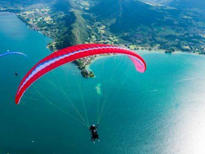 Das Bild zeigt den Gin Gliders Fuse 2. Bei dem Gleitschirm handelt es sich um einen Tandemschirm. Das Bild stellt den Schirm im Flug über einem See dar. Es handelt sich um einen Passagierflug oder auch Tandemflug.