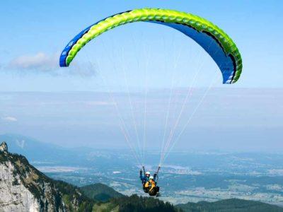 Das Bild zeigt den Tandem Gleitschirm U-Turn Asterion. Es ist ein leichter Tandemschirm und eignet sich für den Passagierflug. Das Bild zeigt die Farbe blau-grün. Das Bild zeigt Pilot und Passagier im Flug.