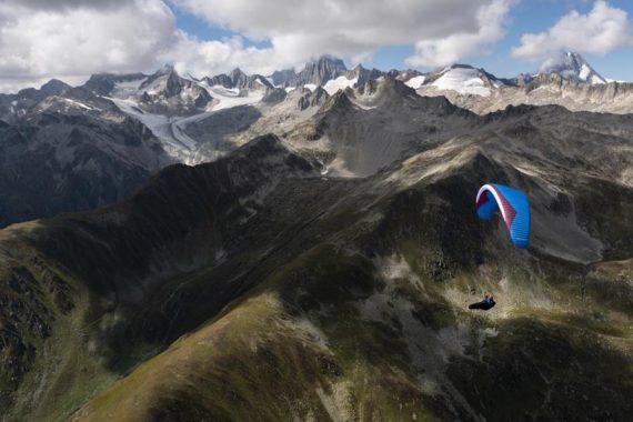 Das Bild ist das Titelbild für die Vorankündigung des Bonanza 2. Dies ist eine neuer XC Gleitschirm von Gin Gliders. Der Paragleiter befindet sich im Flug über den Bergen. Der Pilot sitzt in einem Liegegutzeug. Der Schirm ist in 6 Größen von XXS bis XL erhältlich.