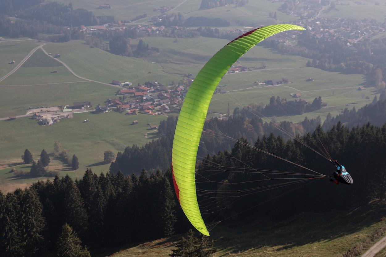 Das Bild zeigt den neuen Bonanza 2 von Gin Gliders. Es ist ein Gleitschirm der Kategorie C. Auf dem Bild befindet sich der Gleitschirm in einer Kurve während eines Testflug bei der oASE Flugschule im Allgäu.